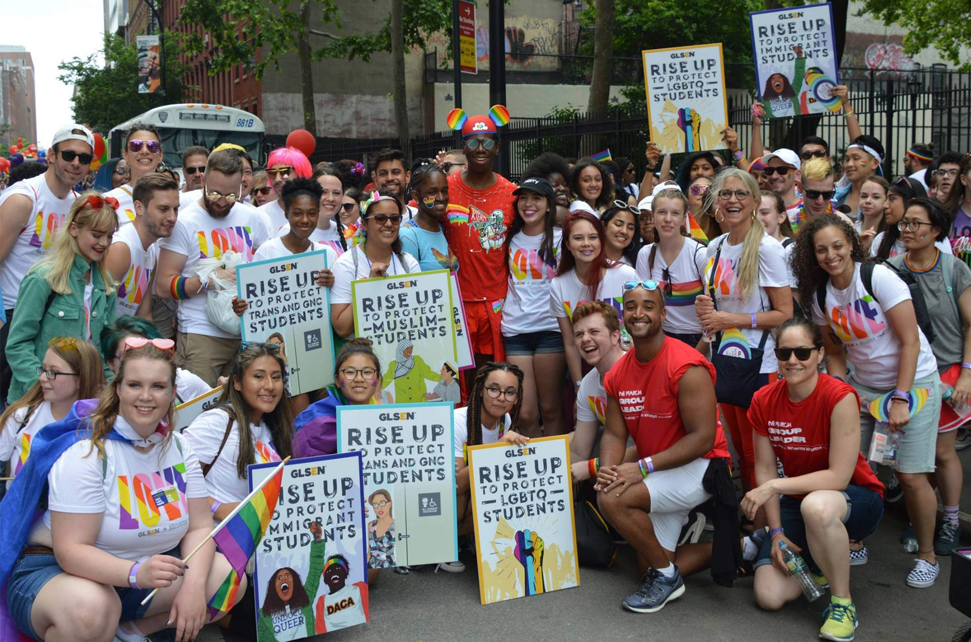 Posed photo of LGBTQ youth with signage