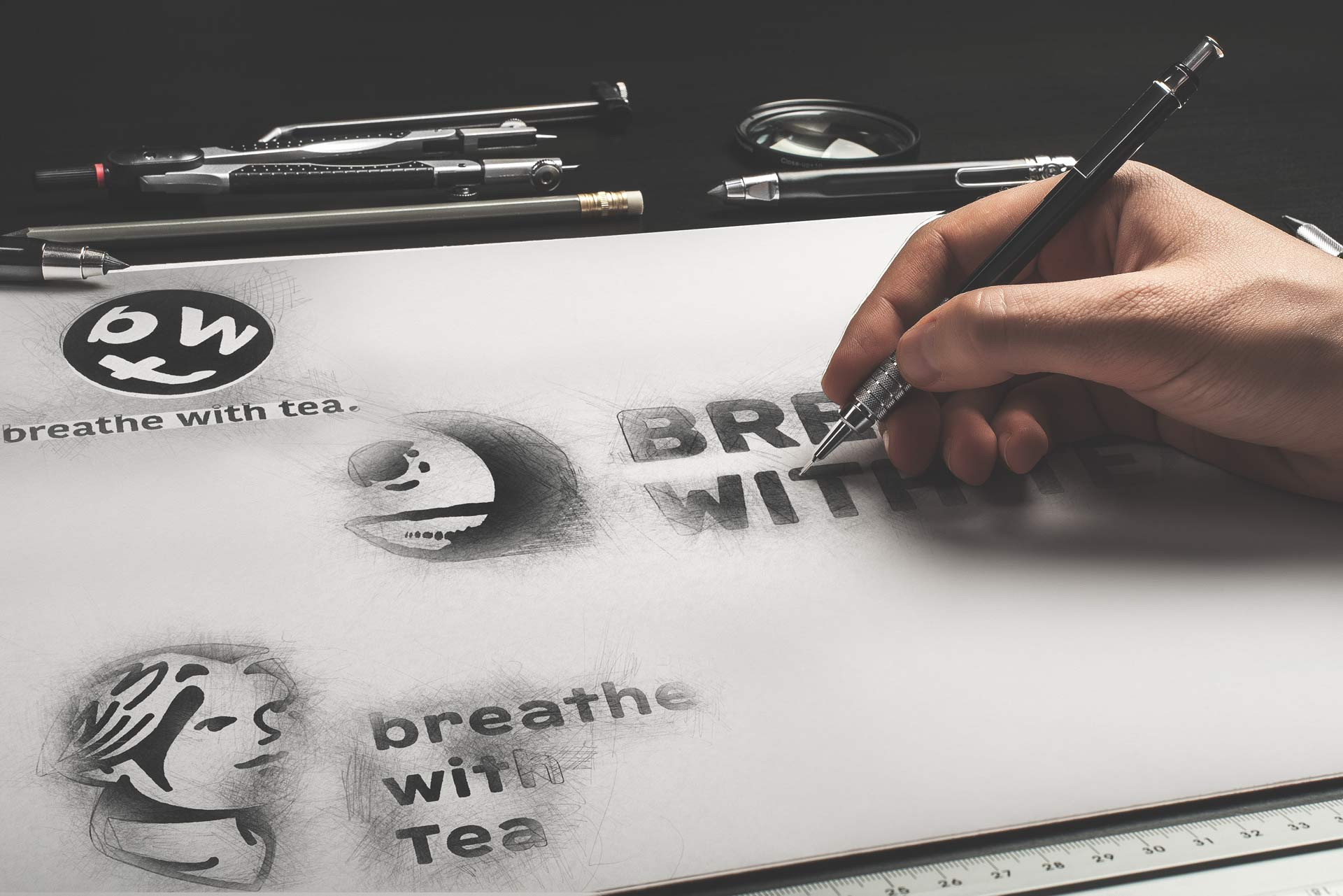 """""""Breathe with Tea"""" logo mockup shows three different logo options on a sketch board. A hand is filling in the logo."""