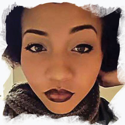 Korryn Gaines real photograph. She has an afro and is wearing a scarf.